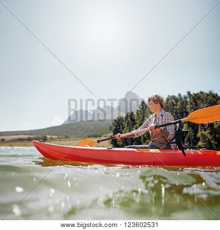 Portrait of a mature woman with kayak in a lake. Senior woman paddling kayak on a summer day.