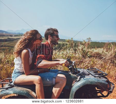 Couple Driving Off-road With Quad Bike