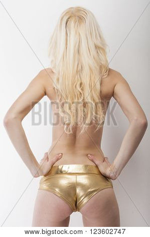 Sexy blonde shows her sexy buttocks in golden hot pants capture from behind