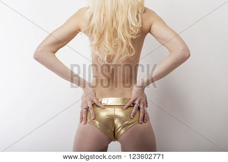 Sexy blonde shows her buttocks in golden hot pants capture from behind