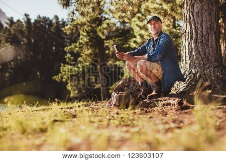 Senior Male Hiker In Forest With A Compass