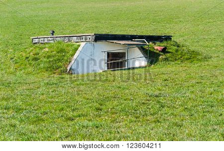 outdoor scenery showing a bunker in overgrown grassy ambiance