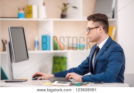 Young businessman with suit working in office. Businessman using computer. Office interior with bookcase