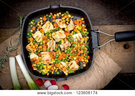 Grilled - roasted chicken meat (chicken breast) and vegetables in pan on rustic wooden background
