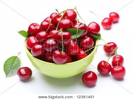 Bowl with ripe cherries and some cherries near the bowl. Isolated on a white background.