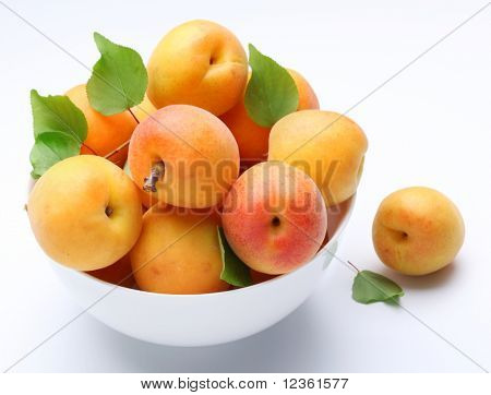 Crockery with mellow apricots. Isolated on a white background.