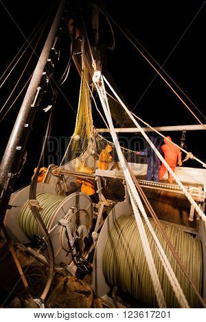 Fishermen standing at the stern of small fishing vessel. Night time.