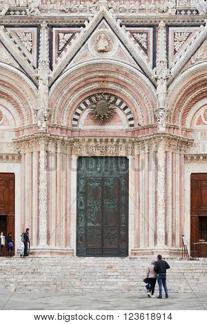 Siena, Italy - Febuary 16, 2016: Front doors of Siena Cathedral, a medieval church built in the Romanesque and Italian Gothic style. It is famous for the beauty and architectural features.