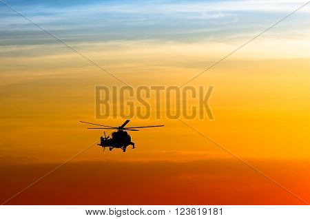 silhouette of the military helicopter at sunset