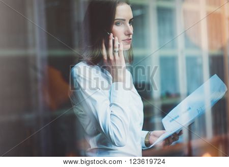 Photo business woman wearing white shirt, talking smartphone and holding documents in hands. Open space loft office. Panoramic windows background.