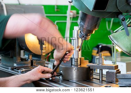 Close up view of the arms of a blue collar worker working on industrial machinery in an engineering factory or workshop