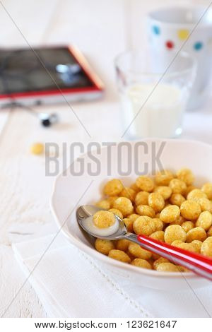 ?orn flakes in bowl milk and tablet pc