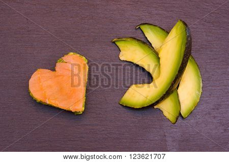 Slices of avocado and avocado and smoked salmon in a heart shape on top in slate seen from above