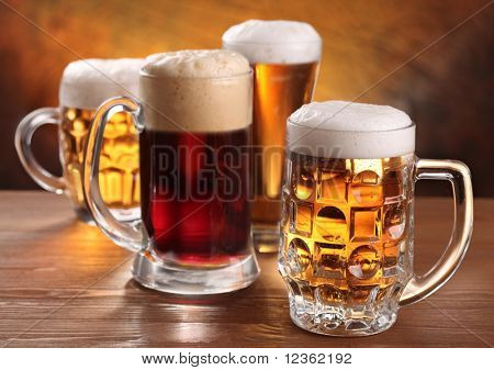 Jarras de cerveza fresca sobre mesa de madera.