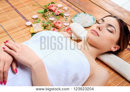 Beautiful young woman at a spa salon resting on a straw mat. Concept of relaxation