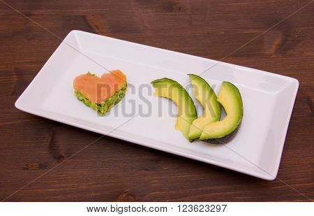 Slices of avocado and avocado and smoked salmon in the shape of heart on tray on wood