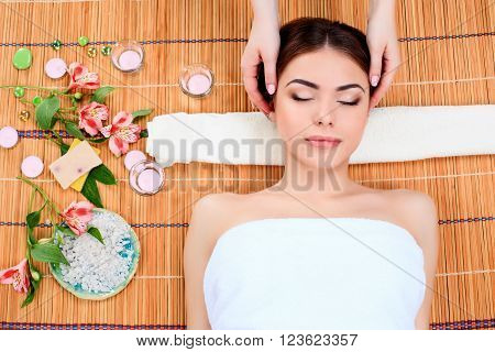 Beautiful young woman at a spa salon resting on a straw mat with flowers. The girl taking a beauty treatment