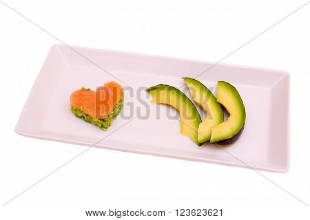 Tray with slices of avocado and salmon and avocado in a heart shape on white background