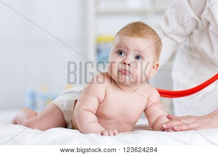 doctor examining baby with stethoscope in consulting room