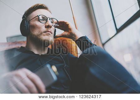 Closeup photo handsome bearded man glasses in headphones listening to music modern loft studio.Man sitting in vintage chair, holding smartphone and relaxing.Panoramic windows background, film effect.
