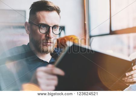 Portrait handsome bearded businessman wearing glasses, black shirt.Man sitting in vintage chair modern loft studio, reading book and relaxing.Time break. Blurred background, film effect.