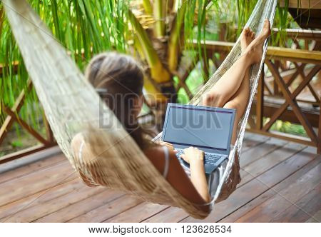 Young beautiful woman lying in a hammock with laptop in a tropical resort. back view.