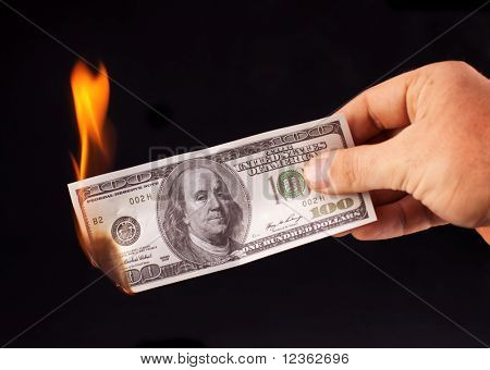 burning dollar in hand isolated on a black