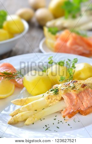 Gratinated white asparagus with smoked salmon and cheese sauce, served with boiled potatoes and lemon
