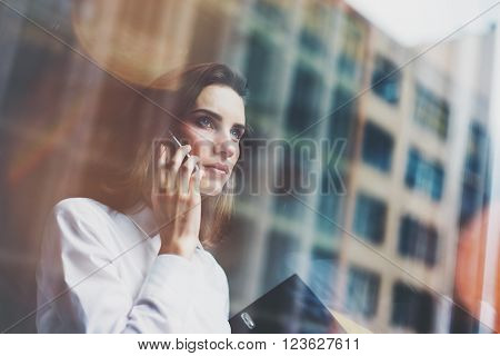 Photo business woman wearing modern white shirt, talking smartphone and holding documents in hands. Open space loft office. Panoramic windows background. Horizontal mockup.