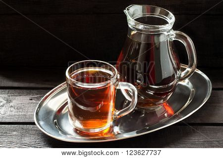 Traditional Russian drink kvass made from bread rye malt sugar and water. Kvass in the jug and mug on a dark wooden background