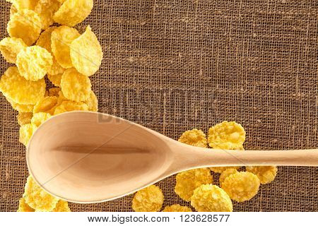 Wooden spoon and corn flakes on sack background closeup