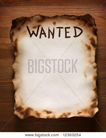 """La palabra """"Wanted"""" se escribe en una textura de papel viejo en el fondo de una pared de madera"""
