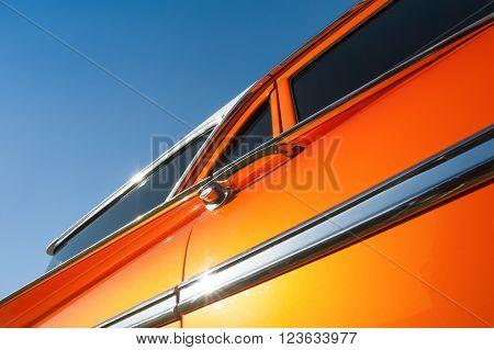 metallic orange vehicle panel with blue sky