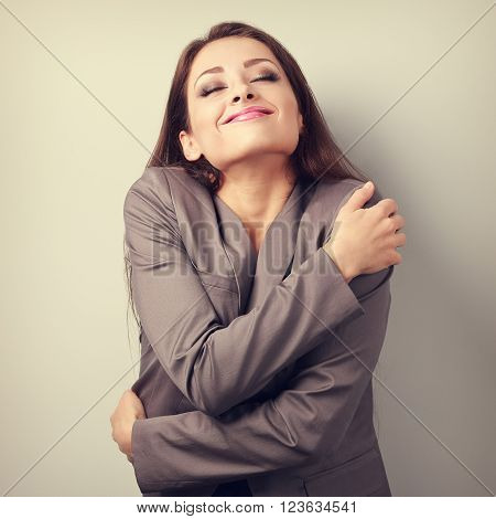 Happy business woman hugging herself with natural emotional enjoying face. Love concept of yourself. Toned portrait
