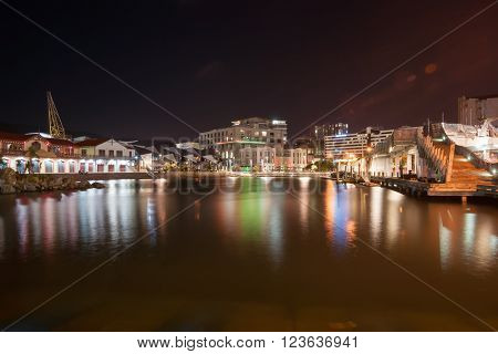 City lights reflected in colorful display on calm harbor water  across bay Wellington New Zealand