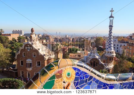 Barcelona, Spain - November 10, 2015: Park Guell entrance buildings and mosaic bench. The Park Guell is a public park system composed of gardens and architectonic elements. The park was built between 1900 and 1914 and was designed by Antoni Gaudi.