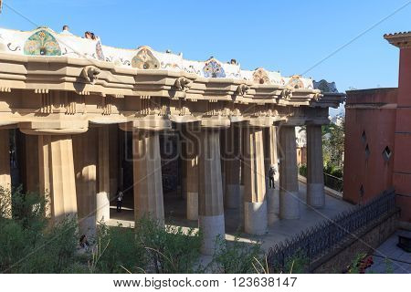 Barcelona, Spain - November 10, 2015: Park Guell Sala Hipostila columns and main terrace. The Park Guell is a public park system composed of gardens and architectonic elements. It was built between 1900 and 1914 and was designed by Antoni Gaudi.