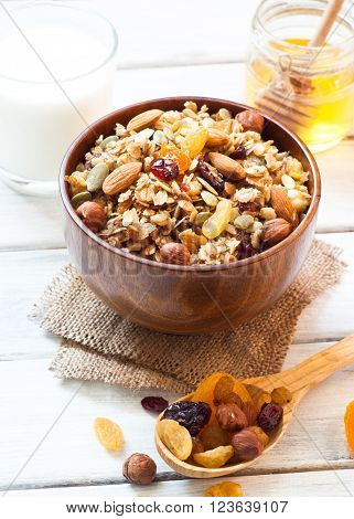 Granola cereal flakes with dried fruit, nuts and honey in a wooden bowl.
