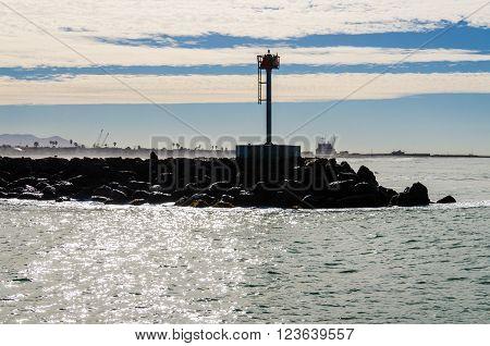 A rocky pier in Oxnard, California with cloudy sky