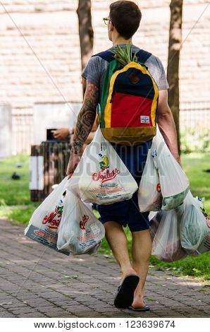 Montreal, Canada - July 26, 2014: A man walks and invents a clever way to carry many grocery bags in Montreal, Canada