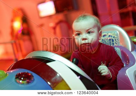 Baby boy playing arcade game machine at an amusement park