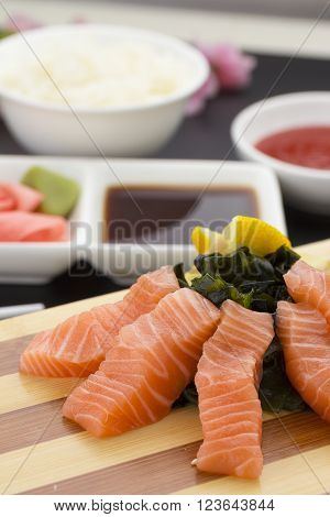 Japanese Cuisine. Salmon Sashimi On A Wooden Plate With Ginger Wasabi And Sauces Over Black Backgrou