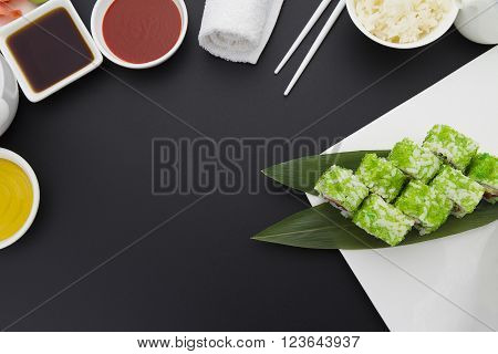 Japanese Cuisine. Sushi Roll With Green Tobiko On A White Plate With Ginger Wasabi And Sauces Over B