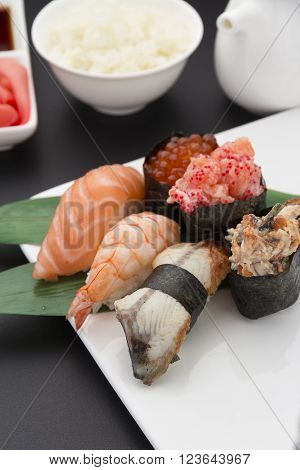Japanese Cuisine. Sushi Nigiri Set On A White Plate With Ginger Wasabi And Different Sauces Over Bla