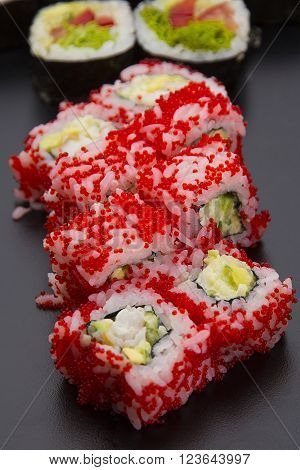 Sushi Roll With Vegetables And Red Tobiko Over Black Background
