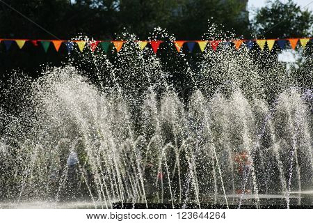 Rows of fountain water jets spraying water into the air in a public park on a sunny summer day and decoratoon of red flags over