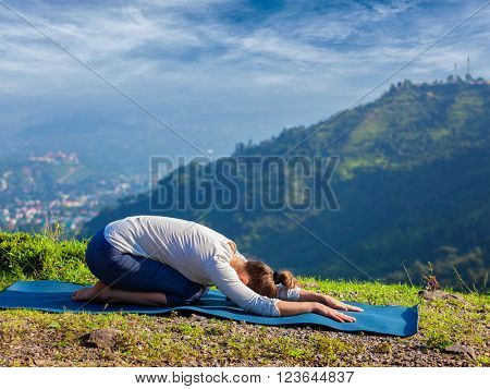 Sporty fit woman practices yoga asana Balasana - child pose outdoors in mountains