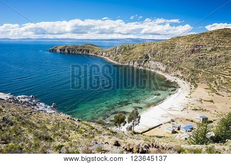 Scenic Caribbean bay with white sand beach on the Island of the Sun, Titicaca Lake, among the most scenic travel destination in Bolivia. Human rural settlement in the backcountry.