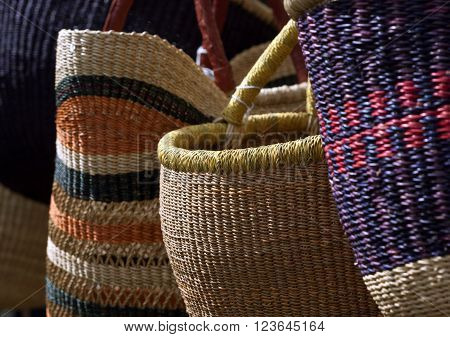 Colorful straw baskets and bags on display for sale at a local market