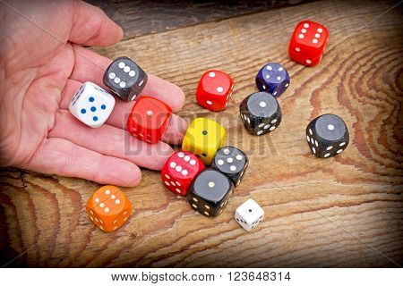 Gambling addiction - Hand throws dice on rustic wooden table